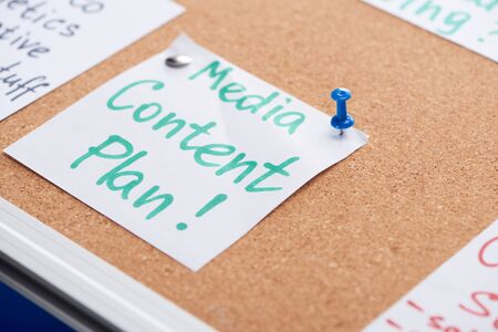 paper card with media content plan inscription pinned on cork office board