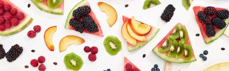 panoramic shot of watermelon on sticks with seasonal berries and fruits on white background