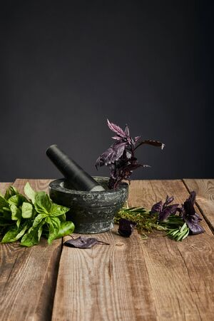 grey mortar with pestle near fresh green and purple basil on wooden table isolated on black