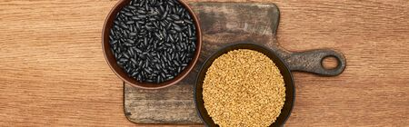panoramic shot of bowls with beans ang grains on wooden cutting board