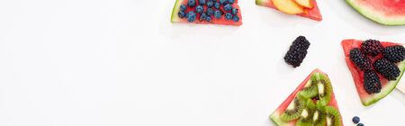 panoramic shot of organic watermelon on sticks with seasonal berries and fruits on white background