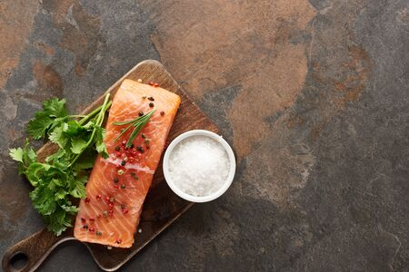 top view of raw fresh salmon with peppercorns, parsley and salt on wooden cutting board