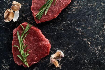 top view of uncooked beef sirloins with garlic and rosemary on black marble background