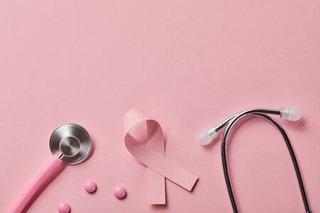 top view of pink metal stethoscope, breast cancer ribbon and three pills on light pink background