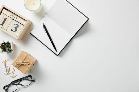 bovenaanzicht van blokken met cijfers en letters, notitieblok, pen, bril, plant en kaars op wit oppervlak