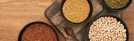 panoramic shot of bowls with roasted buckwheat, chickpea and beans near wooden spoon on wooden cutting boards