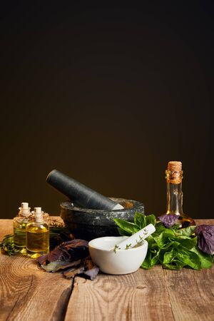 mortars with pestles and bottles with oil near fresh herbs on wooden table isolated on black