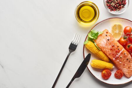 top view of raw salmon steak with corn and tomatoes on plate near cutlery, oil and peppercorns on marble table Archivio Fotografico