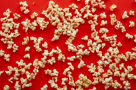 top view of fresh popcorn scattered on red background 스톡 콘텐츠