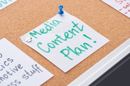 paper card with media content plan lettering pinned on cork office board