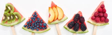 panoramic shot of fresh watermelon on sticks with seasonal berries and fruits on white background 写真素材
