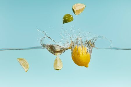 ripe lemon and lime pieces falling deep in water with splash on blue background