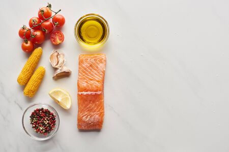 top view of raw salmon steak near lemon, corn, tomatoes, garlic, oil and peppercorns in bowls on marble table