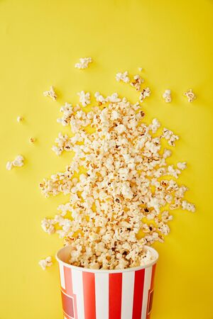 top view of delicious popcorn scattered from bucket on yellow background