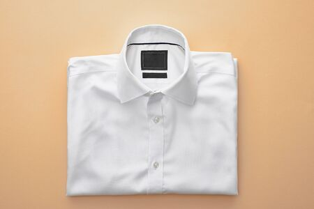 top view of plain white folded shirt on beige background Фото со стока