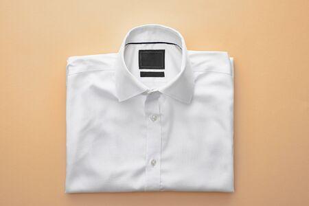 vista dall'alto di una semplice camicia piegata bianca su sfondo beige Archivio Fotografico