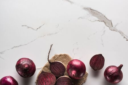 top view of beetroots and red onions on marble surface with hessian