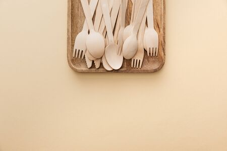 top view of rectangular wooden dish with forks, knifes and spoons on beige background Stock fotó