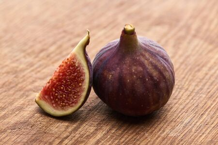 ripe whole and cut delicious figs on wooden chopping board 版權商用圖片