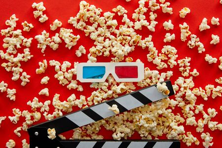 top view of delicious popcorn scattered on red background near clapper board and 3d glasses