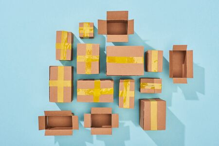 top view of closed and open cardboard boxes on blue background