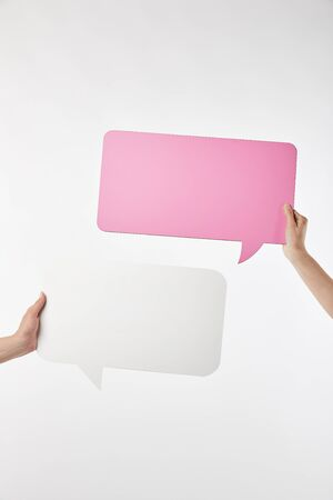 cropped view of two women with speech bubbles in hands isolated on white