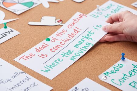 cropped view of woman pinning card with notes pinned on cork board
