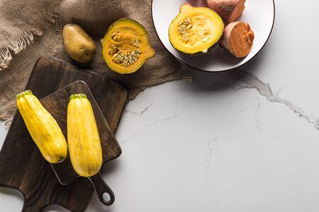 top view of wooden cutting boards with zucchini, potato, pumpkin and plate with yam on marble surface with hessian Фото со стока
