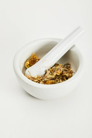 mortar and pestle with herbal tea blend on white background