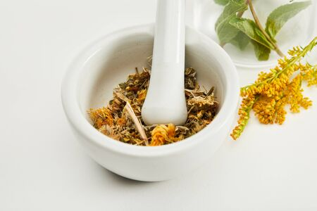 mortar and pestle with herbal mix near goldenrod twig on white background Archivio Fotografico