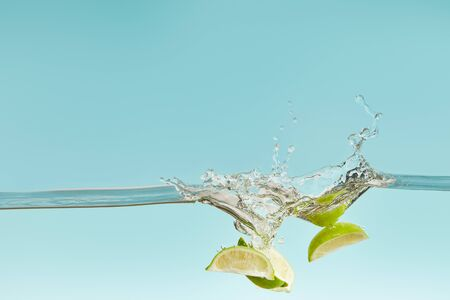 ripe lime pieces falling deep in water with splash on blue background