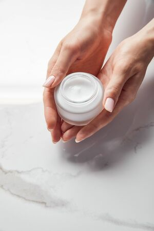 Vista recortada de mujer sosteniendo jar con crema sobre superficie blanca
