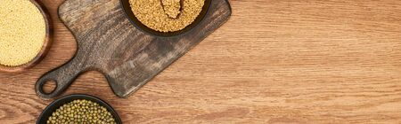 panoramic shot of bowls with couscous and beans on wooden cutting board