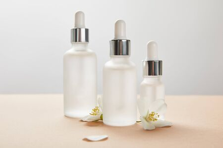 three cosmetic glass bottles with serum and few jasmine flowers with shadow on beige