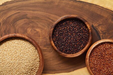 top view of white, black and red quinoa in wooden bowls