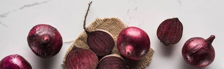 panoramic shot of red onions and beetroots on marble table with hessian