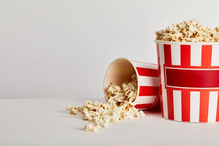 delicious popcorn scattered from red striped paper buckets isolated on grey 版權商用圖片