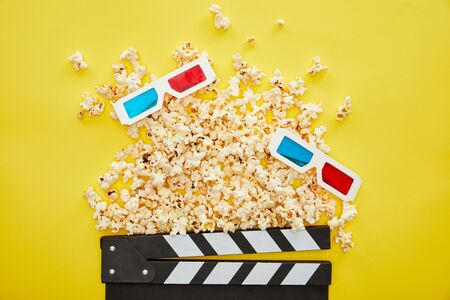 top view of delicious popcorn, 3d glasses and clapper board on yellow background