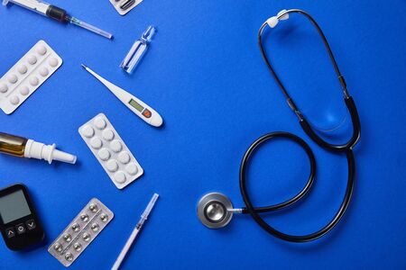 top view of stethoscope near various medical supplies on blue background