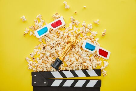 Kiew, UKRAINE - 13. AUGUST 2019: Draufsicht auf leckeres Popcorn, 3D-Brille und Klappbrett mit goldener Oscar-Statuette auf gelbem Hintergrund