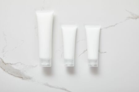 top view of cosmetic cream tubes on white surface