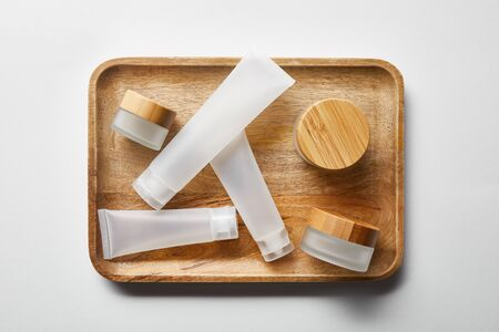 top view of few empty jars and cream tubes on wooden tray on white