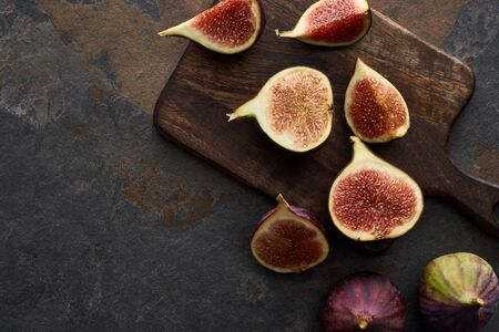 top view of ripe fresh delicious figs on cutting board on stone background