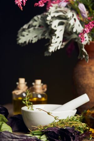 white mortar with pestle near bottles and vase with fresh flowers on wooden surface isolated on black