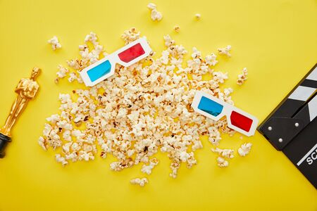 top view of popcorn, 3d glasses and clapper board with golden Oscar statuette on yellow background