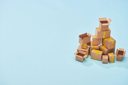 pile of cardboard boxes on blue background with copy space