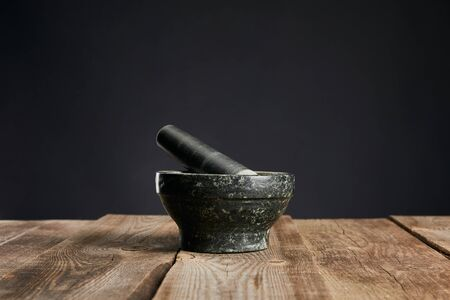 grey stone mortar on wooden table isolated on black