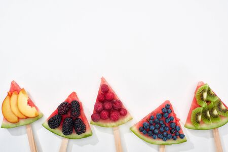 top view of fresh watermelon on sticks with seasonal berries and fruits on white background with copy space