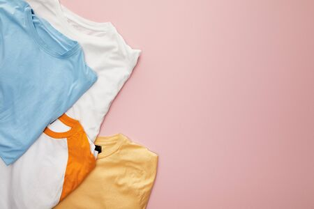 top view of white, yellow, orange and blue folded t-shirts on pink background