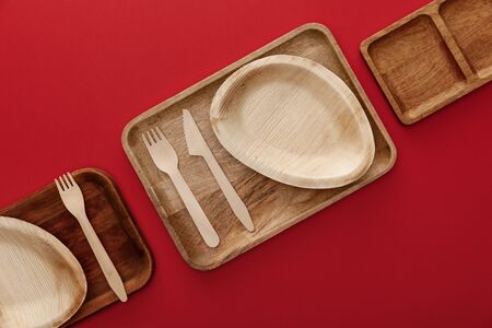 top view of rectangular wooden dishes with plates and cutlery on red background